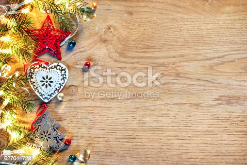 istock . Decorated fir tree with lights on wooden board 627044728