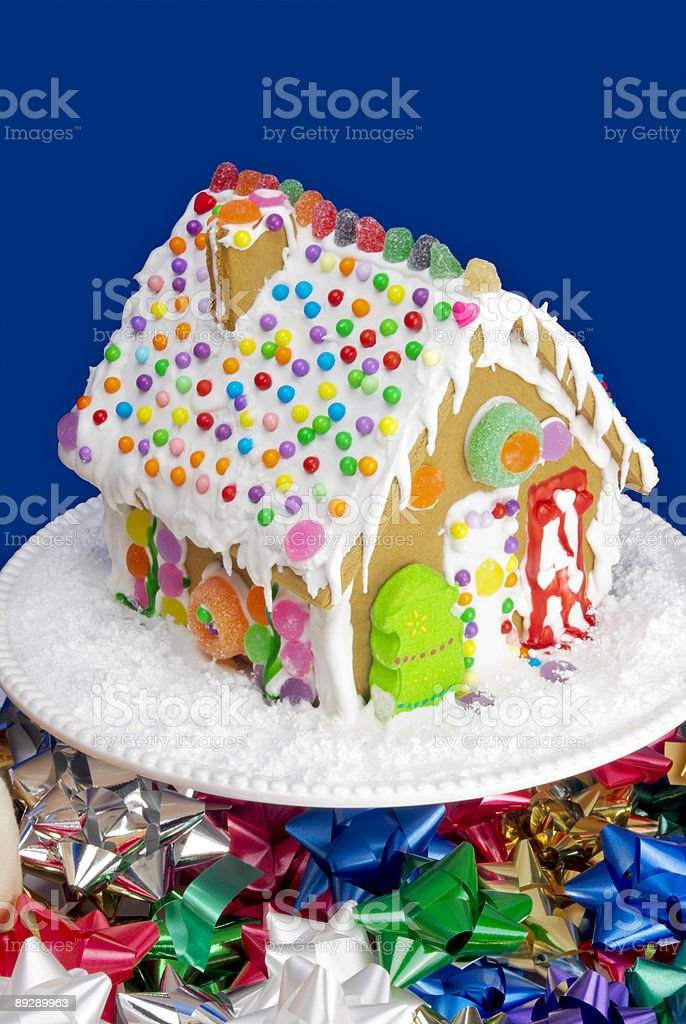 Decorated gingerbread house on a cake stand and Christmas bows royalty-free stock photo