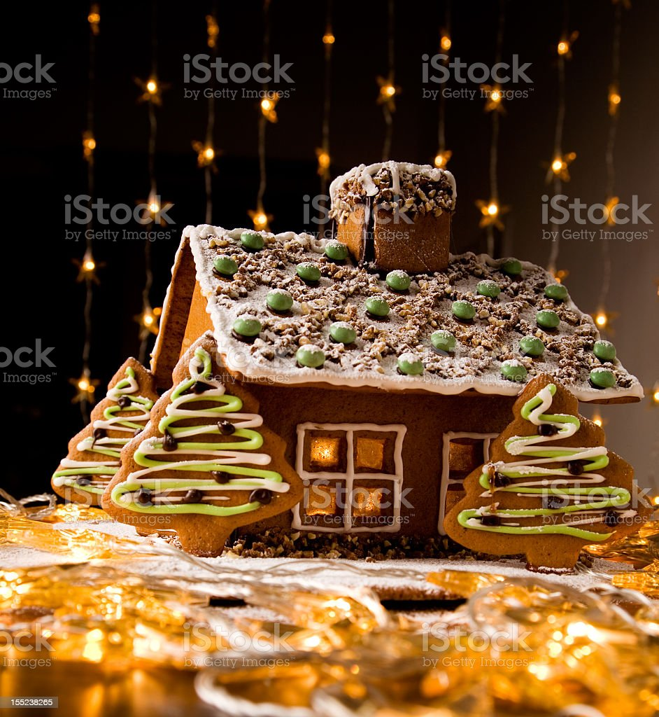 Decorated gingerbread house with trees & lights surrounding royalty-free stock photo