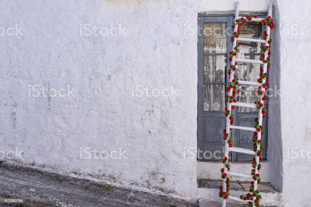 Decorated ladder with green and red flowers on vintage old white wall with copy space as starting Christmas holiday stock photo