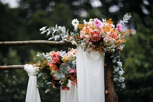 Decorated luxury wedding ceremony arch in the garden.