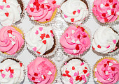 Top view of arranges pink and white colored frosting cream cupcakes decorated with heart sprinkles.