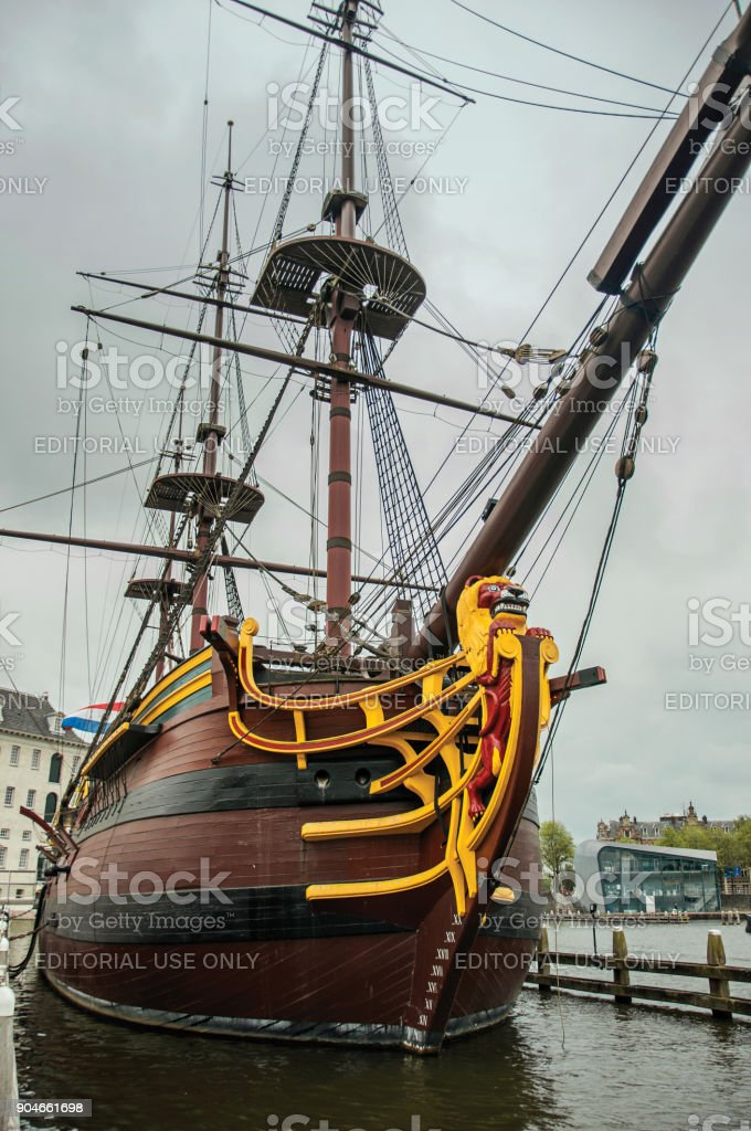 Decorated prow and masts of the sailboat replica moored at dock in Amsterdam. stock photo