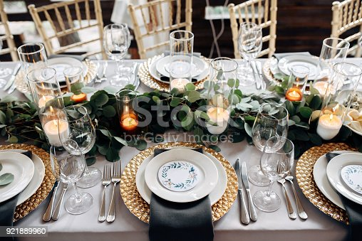 istock Decorated table with gold plates, candles and greens on the white tablecloth 921889960