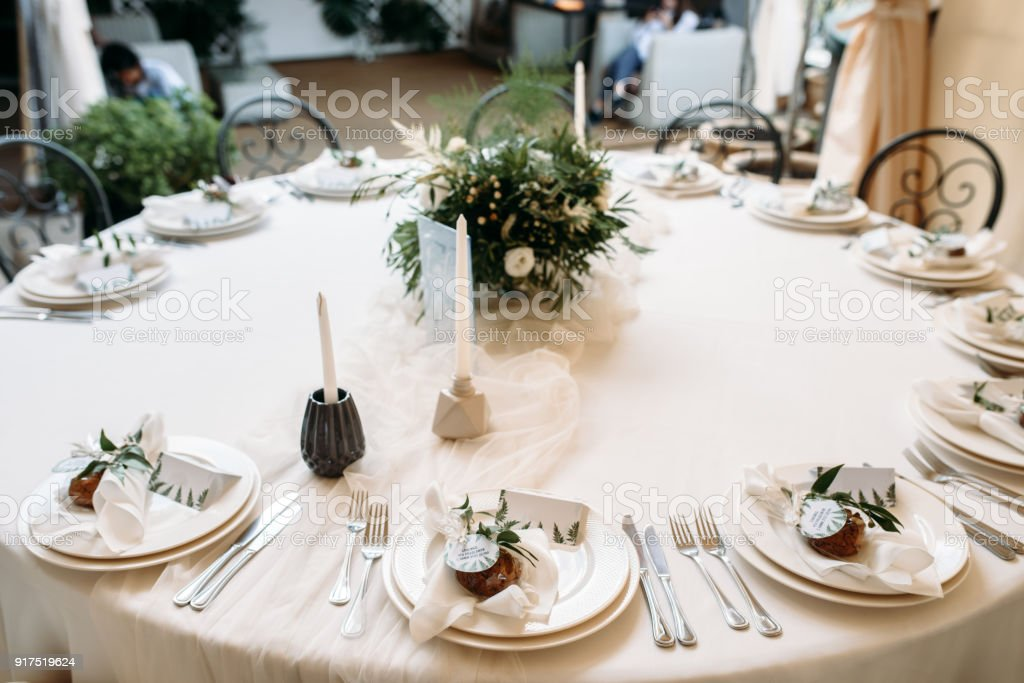 Decorated tables with plates, knives, forks and bouquet with white...