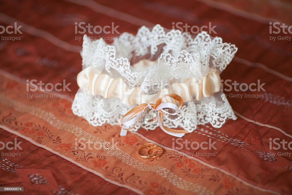 Decorated wedding garter with golden rings. Marriage concept royaltyfri bildbanksbilder