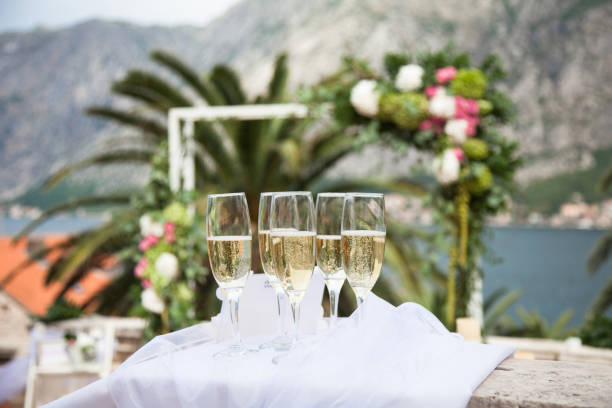 Decorated wineglasses with champagne are on wedding ceremony near wedding arch, mountains, sea, palm. stock photo