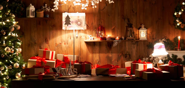 decorated xmas table with merry christmas gifts in cozy santa home interior, banner. happy new year presents boxes in workshop late in night with lights on xmas tree, holiday eve background. - fundo oficina imagens e fotografias de stock
