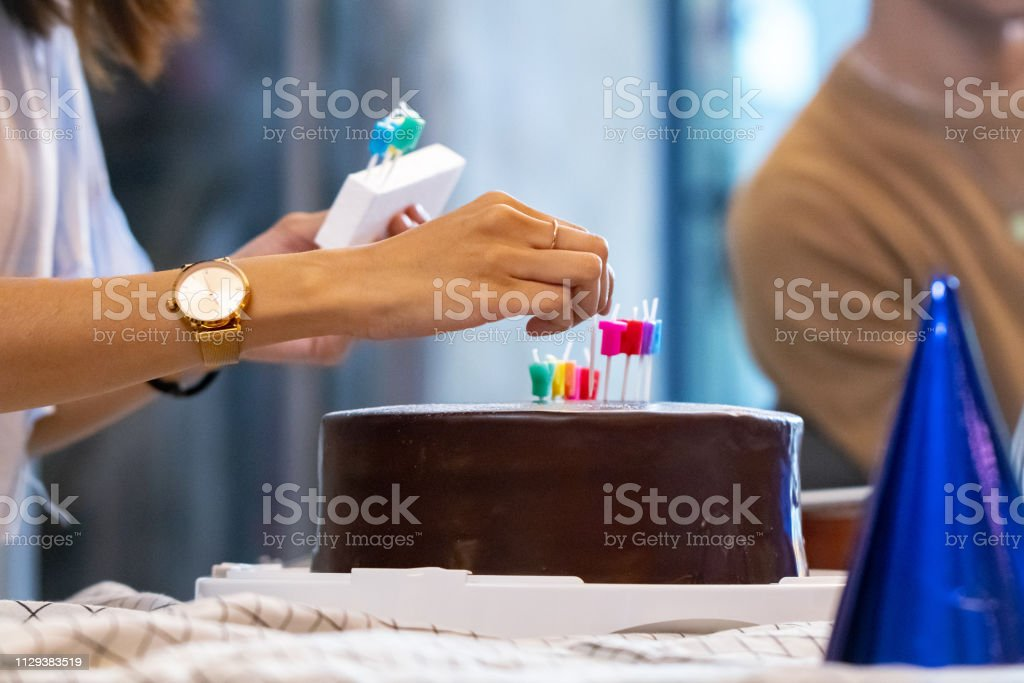 Decorative candles on chocolate cake at birthday party.