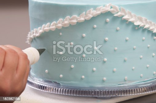 Frosting decorations to a light blue wedding cake