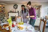 Photo of multi ethnic couple decorating a Christmas table for a Christmas dinner