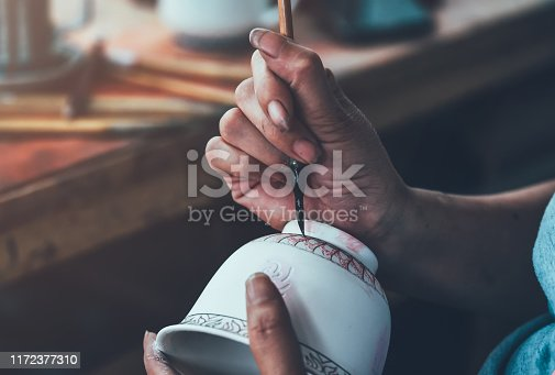 A worker is decorating a porcelain cup in a ceramic factory in China.
