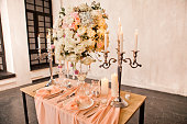 Wedding table setting with beautiful tablecloths, expensive dishes and decorations
