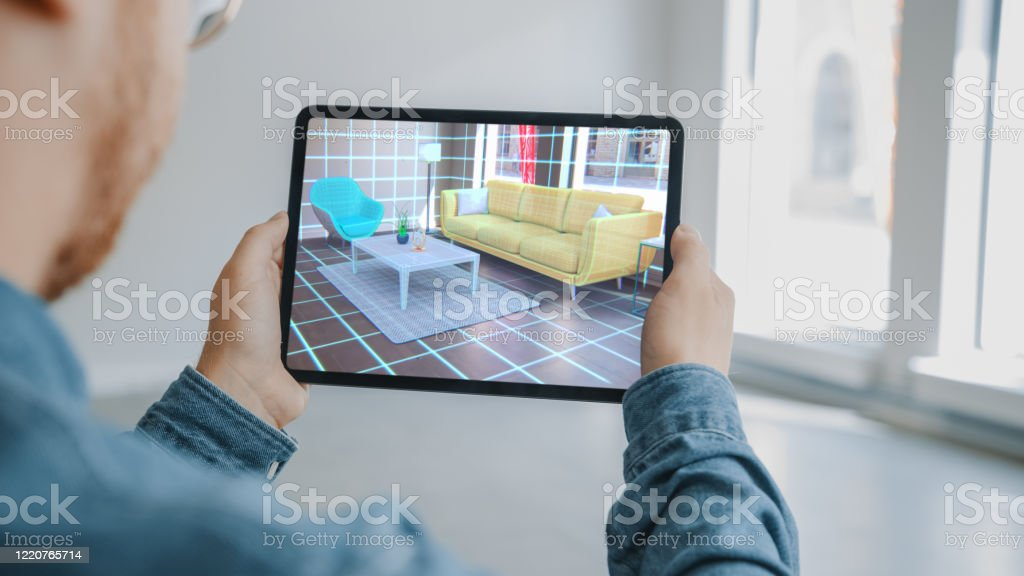 Decorating Apartment Man Holding Digital Tablet With Ar Interior Design Software Chooses 3d Furniture For Home Man Is Choosing Sofa Table For Living Room Over Shoulder Screen Shot With 3d Render Stock