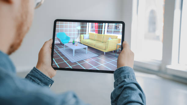 Decorating Apartment: Man Holding Digital Tablet with AR Interior Design Software Chooses 3D Furniture for Home. Man is Choosing Sofa, Table for Living Room. Over Shoulder Screen Shot with 3D Render stock photo