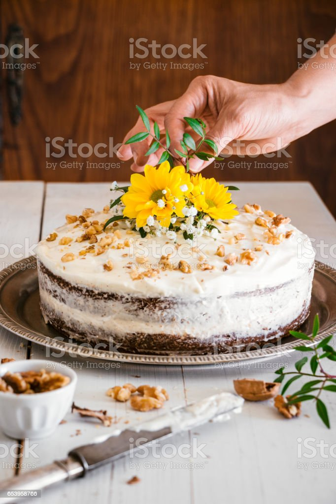 Decorating carrot cake with flowers stock photo