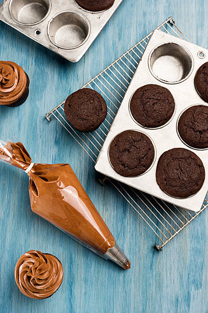 Decorating Chocolate Cupcakes With Frosting After cooling, the chocolate cupcakes are topped with frosting from the pastry bag. icing bag stock pictures, royalty-free photos & images