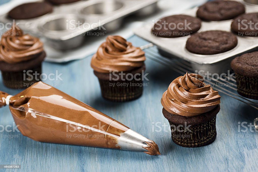 Decorating Chocolate Cupcakes With Frosting royalty-free stock photo