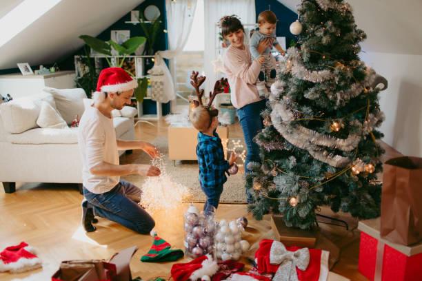decorating christmas tree - украшать стоковые фото и изображения