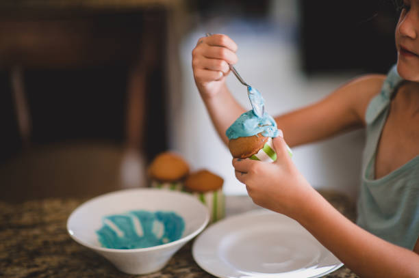 Decorating cupcake with blue icing sugar stock photo