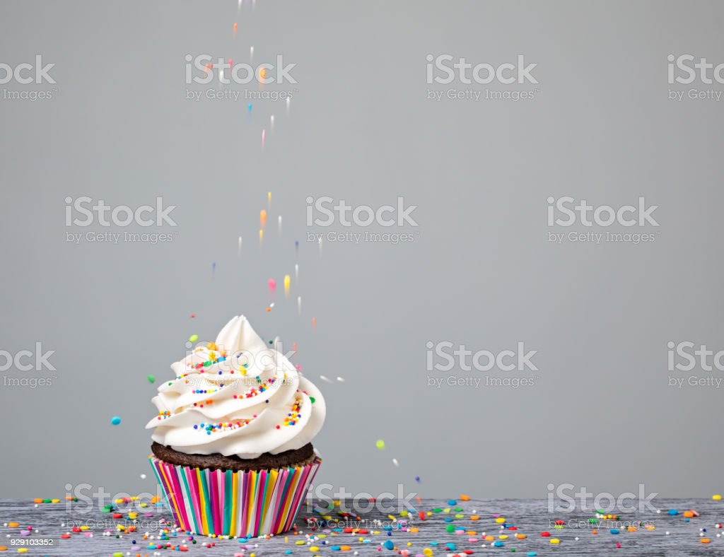 Decorating Cupcake with Sprinkles stock photo