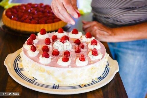 istock Decorating delicious raspberry cream cake kitchen woman hand 171356946