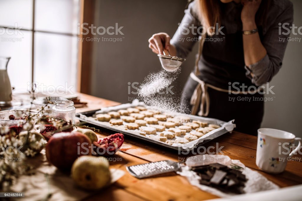 Decorating Gingerbread Cookies With Powdered Sugar stock photo