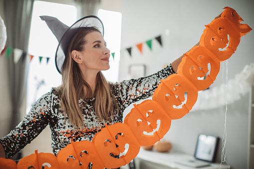 Mature woman in costume decorating home for Halloween, everything need to be perfect when family gather around, she is hanging different type of garlands