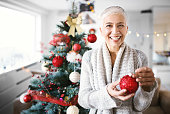 One senior woman decorating the Christmas tree. She is smiling and looking at camera.
