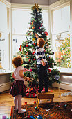 A young red head boy and his sister are decorating the Christmas tree in their home. He is reaching up and putting a bauble onto the tree while his sister watches on.