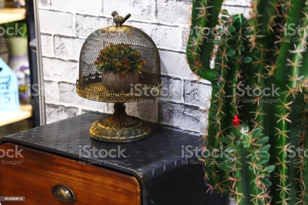 Decoration and interior design. On the antique vintage table stands a decorative decorated openwork metal cage for birds with a flower inside and next to a cactus. stock photo