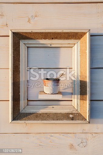 Decoration at the New Year's fair - a pot with flowers in picture frame. A spaced composition on a white wooden background.