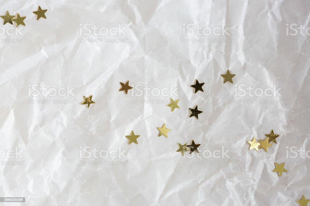 decoración, Fondo, textura concepto. estrellitas doradas brillantes están brillando en el fondo de papel arrugado para envolver los regalos para las vacaciones - foto de stock