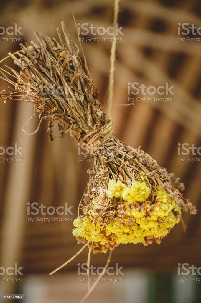 Dekorasyon, buket, baş aşağı bir ipte asılı küçük sarı çiçek demet. Ahşap backgroung. royalty-free stock photo