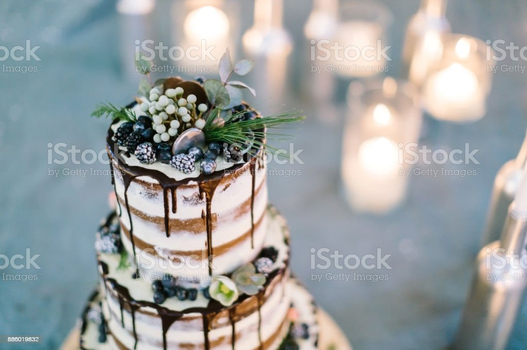 decoration, engagement, treatment concept. close up of top of delicious cake, cooked for celebrating wedding, amazingly decorated with floral elements, blackberries and frosting stock photo