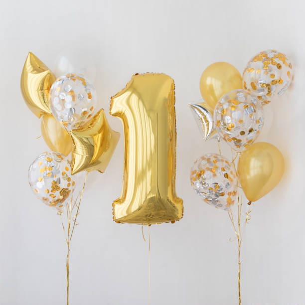 Decoration for 1 years birthday, anniversary Decoration for birthday, anniversary, celebration of the first anniversary, white background and gold balloons first birthday stock pictures, royalty-free photos & images