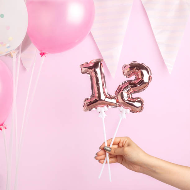 dekoration für geburtstagsfeier. weibliche hand hält goldenen ballon in form von 12 zahl auf rosa hintergrund. - number 13 stock-fotos und bilder