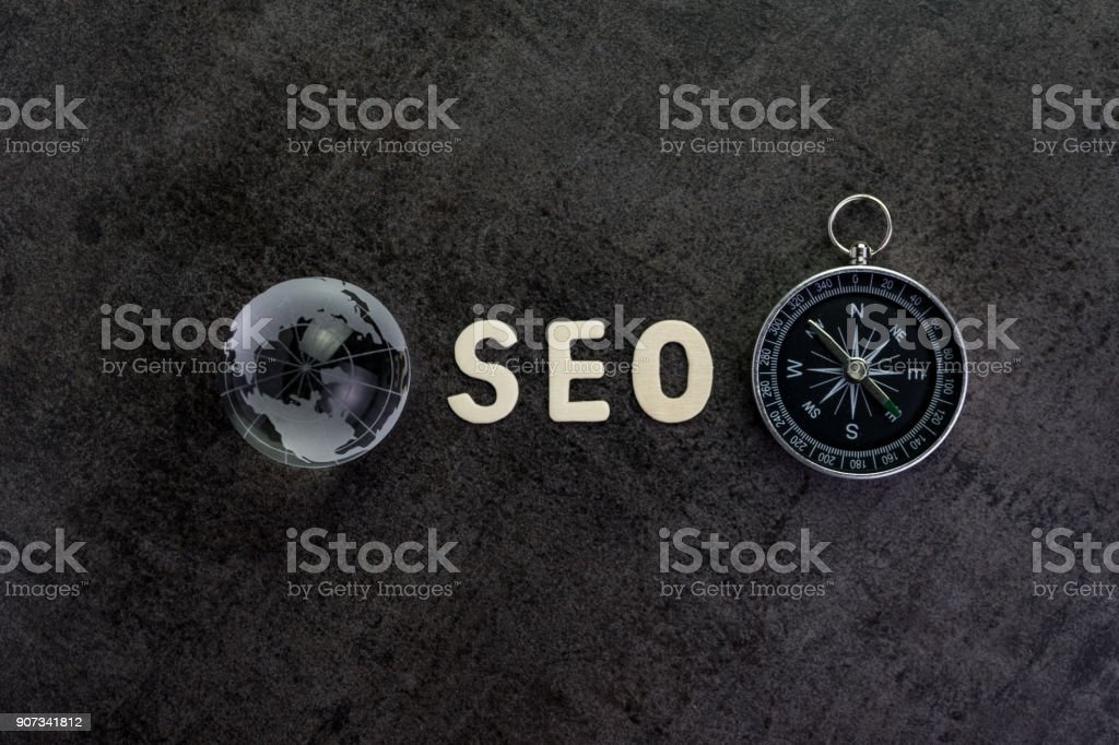 Decoration globe, alphabet SEO and compass on dark cement chalkboard background using as SEO Search engine optimization concept stock photo