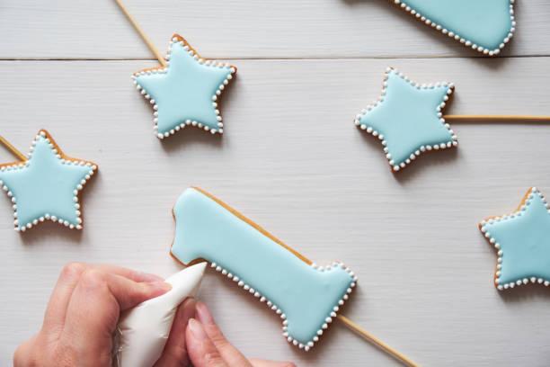 dekoration von lebkuchen in form von sternen und zahlen eins auf einem weißen tisch. - nummer 1 kuchen stock-fotos und bilder