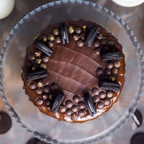 dekoration auf einer schokolade kuchen kekse und schokolade tropfen gold bedeckt. ansicht von oben. flach zu legen - oreo torte ohne backen stock-fotos und bilder