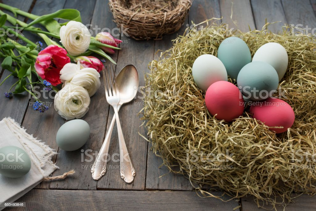 Decoration with easter eggs in a nest and flowers stock photo