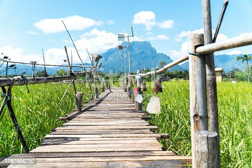 istock Decoration wood bridge at rice field. Decorative wood bridge with row of hanging bell and pinwheel at green rice field with mountain and blue sky background. 1187656732