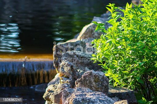 istock Decorative artificial waterfall in summer park. 1328382241