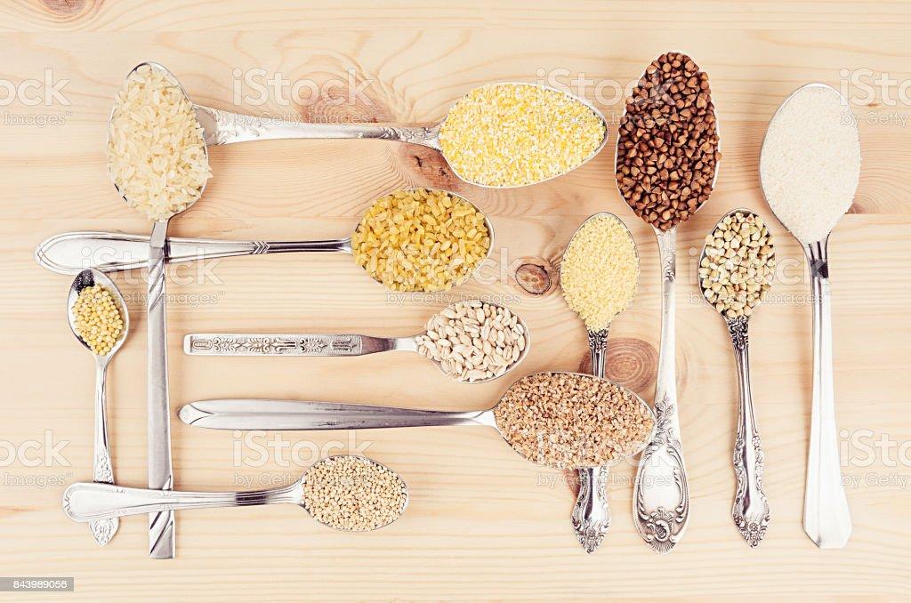 Dekorativer Hintergrund Sortiment Grütze Getreide im silbernen Löffel auf Holzbrett. Gesunde Ernährung-Hintergrund. – Foto