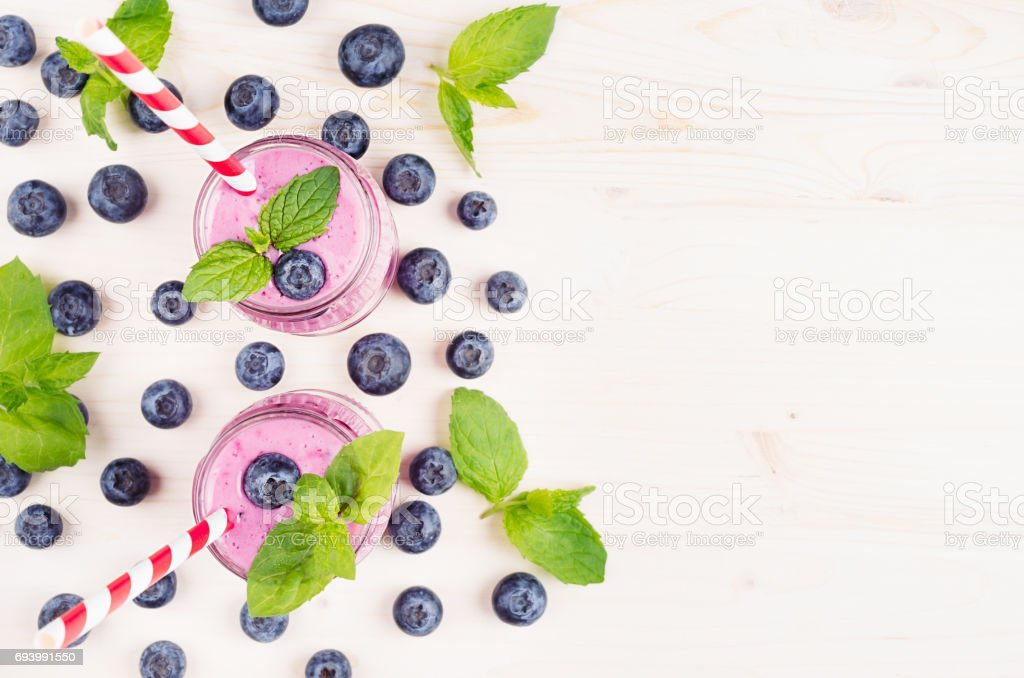 Decorative border of violet blueberry fruit smoothie in glass jars with straw, mint leaves, berries, top view. White wooden board background, copy space.
