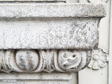 Decorative stone building ledge with carved detail and worn from time