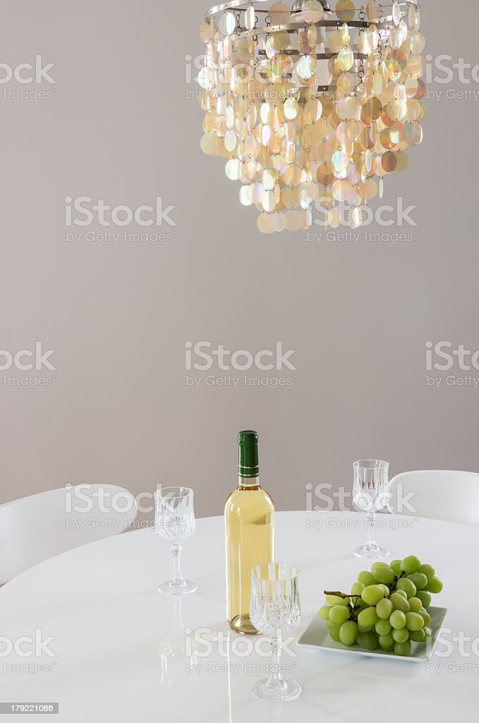 Decorative chandelier and bottle of wine on the table royalty-free stock photo
