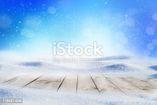 530427918 istock photo Decorative Christmas background with winter snowy blurred bokeh flakes of snow fall and empty wooden flooring 1194311533