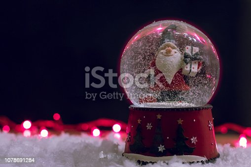 istock Decorative Christmas Snow Globe on a Black Background 1078691284