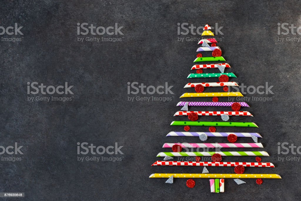 Decorative christmas spruce made of colored pipes on a black background. New Year card.Abstraction. stock photo